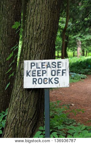 Tall sign that reads ' Please keep off rocks ' set in woodsy area of garden.