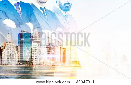 Partnership concept with businespeople crossing arms on New York city background with sunlight. Double exposure