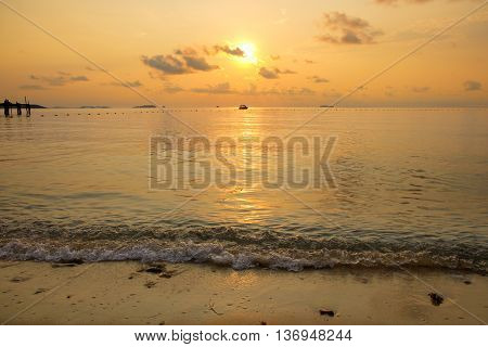 Seascape of beach during sunrise with silhouette of small boat at Ao Lung Dam beach in Samet island Thailand.
