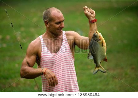 Man fishing with piranha on the pond