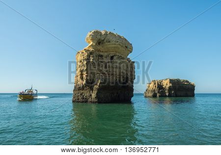 A view of the outlook boat and the rocks on the sea near the Algarve coast in Portugal 2016