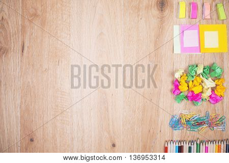 Top view of empty wooden table with colorful stationery items ogranized neatly on its right side. Mock up