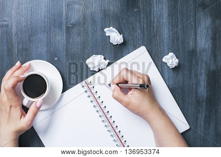 Top view of woman's hand writing in blank spiral notepad and holding coffee cup on wooden desktop with crumpled paper balls. Mock up