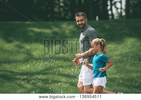 Father and daughter jogging. Side view of cheerful father and daughter jogging in park together