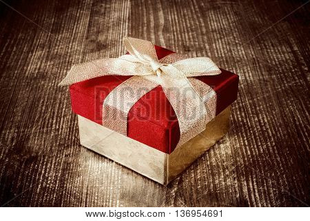 Gift box with golden ribbon on the dark wooden floor