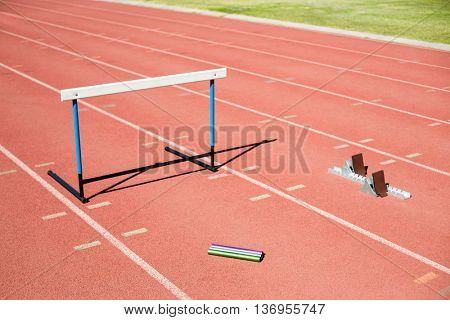 Hurdle, relay baton and a starting block kept on a running track in stadium
