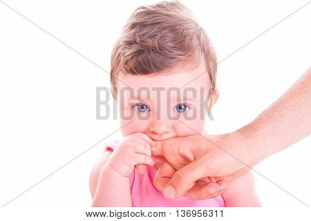 Beautiful baby girl biting daddy's hand on white background.