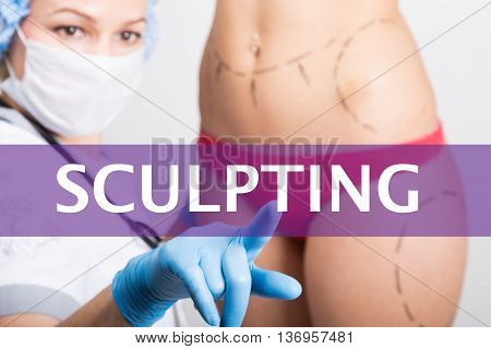 sculpting written on a virtual screen. Internet technologies in medicine concept. medical doctor presses a finger on a virtual screen. cosmetic surgery, lifting and breast augmentation.