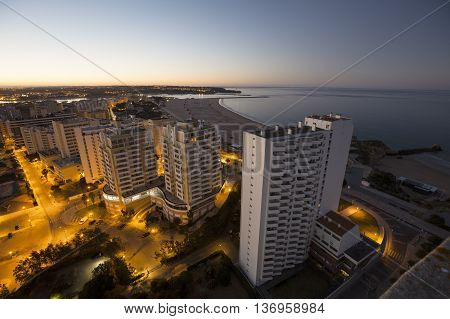 Hotels and beach at the bank of the ocean during sunrise. View from above. Pria Da Rocha Portimao Portugal.