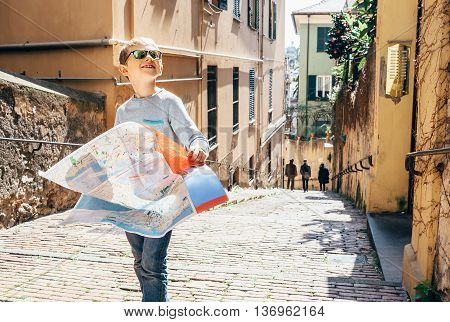 Little boy with city map stay on the old italian street