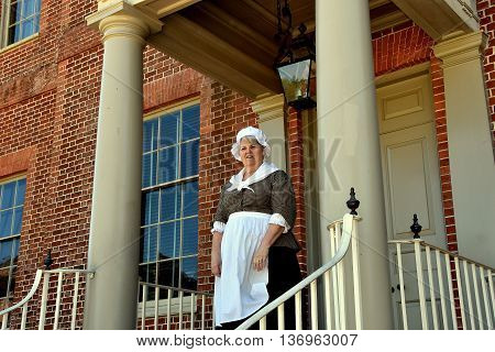 New Bern North Carolina - April 24 2016: Costumed docent in period colonial clothing welcomes visitors at the entrance door to historic 1770 Tryon Palace
