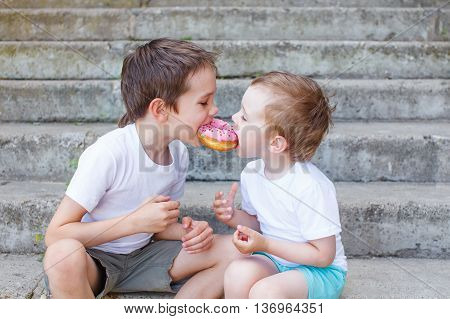 divide the a donut in half. two boys together bite from the donut. children enjoy a donut with strawberry frosting. feeding game for party