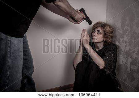 Aggressive man threatening frightened woman with the gun