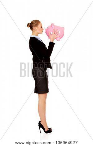 Young business woman kissing a piggybank