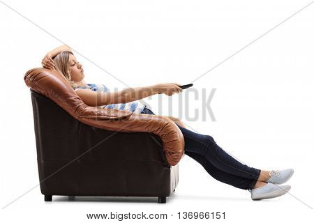 Bored young woman sitting on an armchair and changing channels on TV isolated on white background