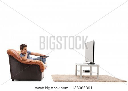 Bored little boy watching TV and changing the channels isolated on white background