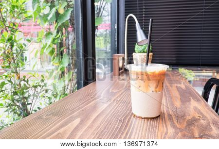 Ice Coffee On Wood Table Beside Window In Coffee Shop At Garden