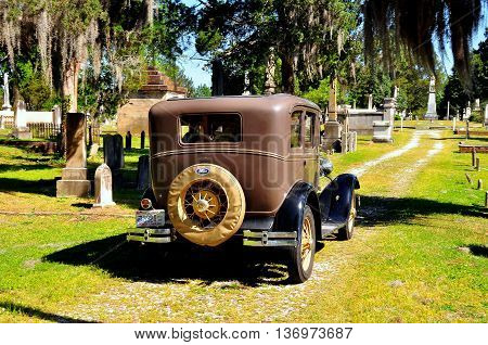New Bern North Carolina - April 24 2016: Vintage 1929 Model A Ford sightseeing vehicle taking visitors for a tour of historic Cedar Grove Cemetery *