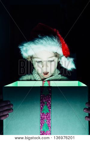 Portrait of surprised boy in Santa hat looking down at Christmas present with open mouth