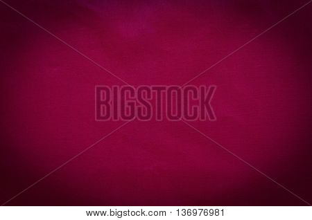Maroon fabric texture. Dark background with textile material.