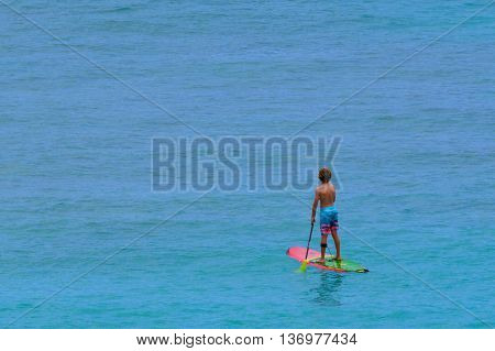 A Boy paddelboarding on a calm Pacific ocean morning in complete solitude