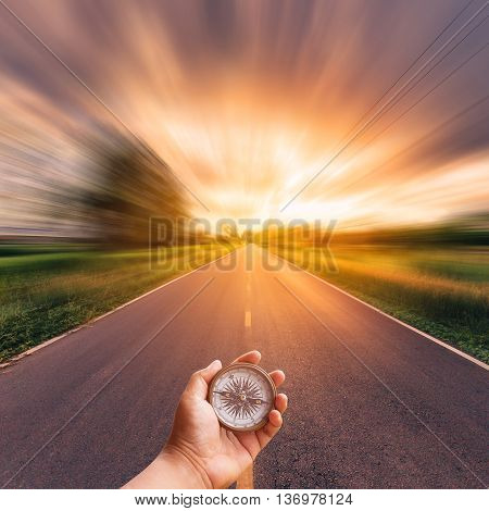 Hand Man Holding Compass On Blurred Road With Sky Sunset.