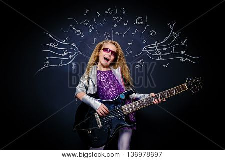Little rock star singing with her electric guitar over musical background. Music concept.