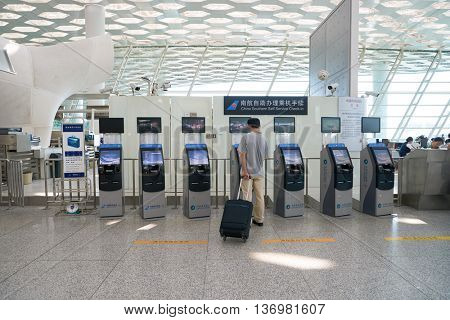 SHENZHEN, CHINA - CIRCA MAY, 2016: man use self check-in kiosk in Shenzhen Bao'an International Airport. It is located near Huangtian and Fuyong villages in Bao'an District, Shenzhen, Guangdong, China