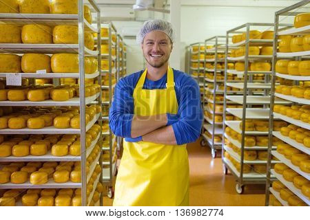 Handsome cheesemaker is checking cheeses in his workshop storage.