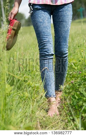 Beautiful young female legs walking on the grass in summer