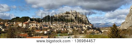 Panoramic view of Sisteron rooftops and the Citadel in summer light with clouds. The Sisteron Citadel and its fortifications is located in the Southern Alps (Alpes de Haute Provence) in the Durance Valley, France