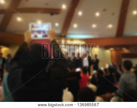 Blurred Background Of Man Recording Video Or Taking Picture By Smartphone