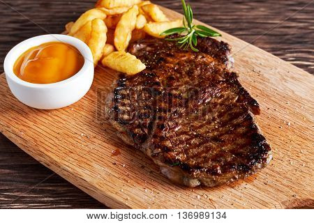 Grilled Beef Steak with Chips and Mango souce on wooden board
