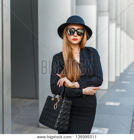 Stylish Fashionable Young Woman In Sunglasses, Hat, Black Shirt And Skirt Holding A Handbag.