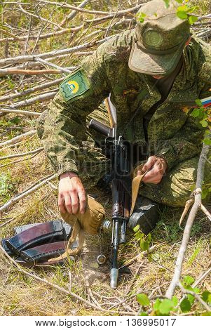 Tyumen, Russia - June 11, 2016: Race of Heroes project on the ground of the highest military and engineering school. Exhibition of weapon. Soldier cools a submachine gun barrel with water from a flask
