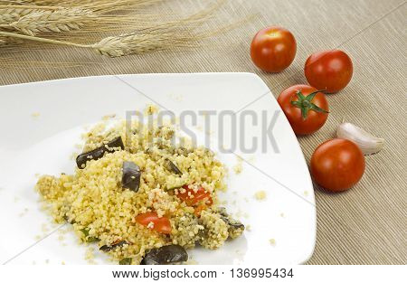 Couscous whit vegetables in a white ceramic plate with wooden background