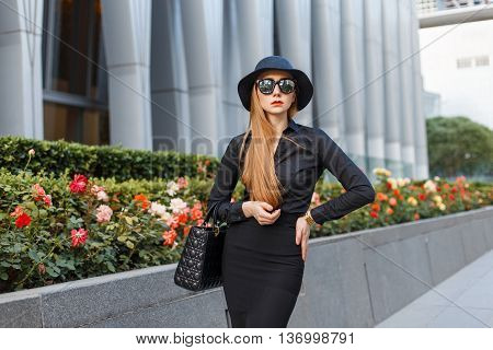 Stylish Young Girl In A Hat And Black Clothing With Sunglasses Against A Background Of A Modern Buil