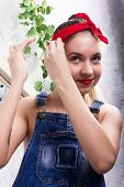 beautiful young woman in denim overalls and a bandana looking at the camera as the mirror, Chupa Chups licking and posing. poster