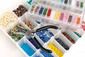 An organizer full of multi colored beads and tools for making jewelry and crafts. poster