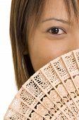 an asian model hides behind a wooden fan poster