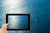 Tablet photography concept. Taking pictures on a tablet. Blue water with sun reflections poster