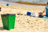 Order and cleanliness at the beach. Tourists resting lying on seaside. Green metal trash can on sand. poster