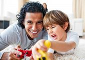 Excited little boy and his father playing video games lying on the floor in the living-room poster