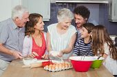 Smiling grandmother cooking food with family in kitchen at home poster