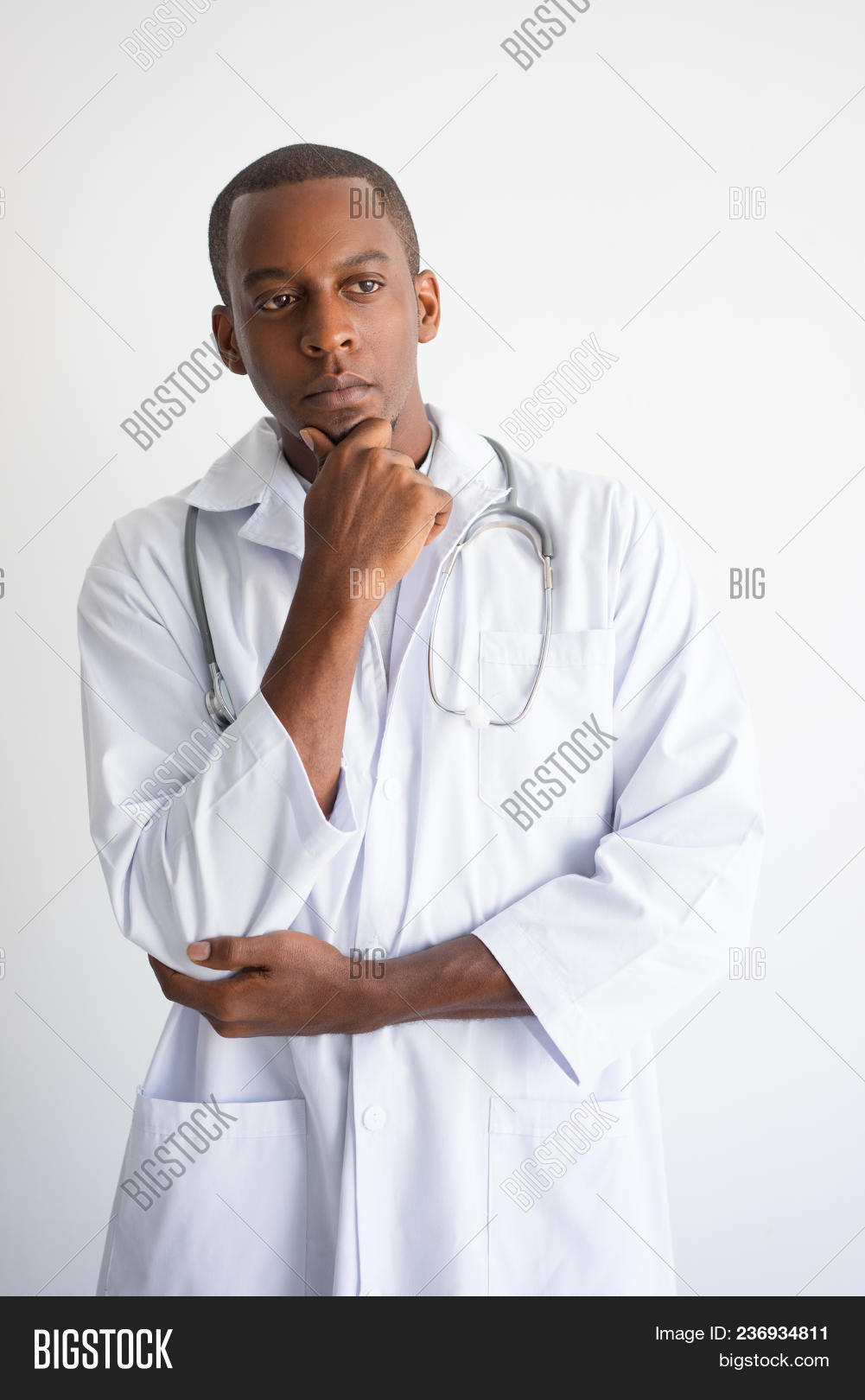 69e6f67d4d4 Pensive black male doctor touching chin. Medical decision concept. Isolated  front view on white background.