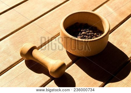 Mortar With Black Pepper And Pestle .  On Wooden Background  .