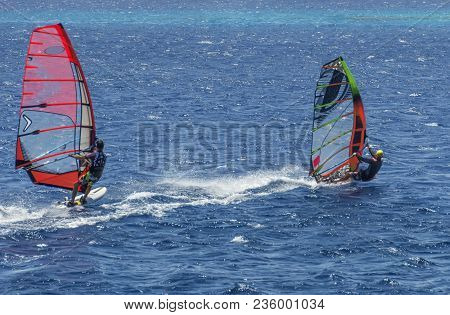 Two Windsurfers On Sailboards Are Moving At A Speed Along The Sea Surface, Against A Background Of W