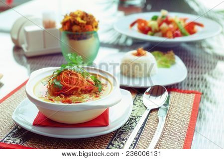 Bowl of spicy curry dish with coconut milk on restaurant table outdoors, toned, grain added