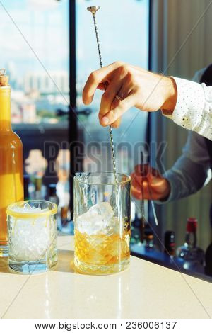 Bartender is stirring cocktail with ice cubes in mixing glass, toned, some grain added