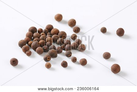 handful of whole allspice berries on white background